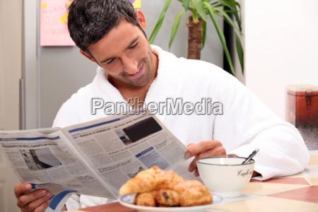 man at kitchen table having breakfast
