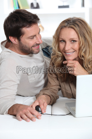 husband looking at wife on laptop