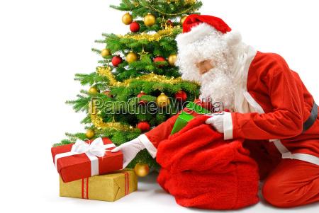 santa claus puts presents under the