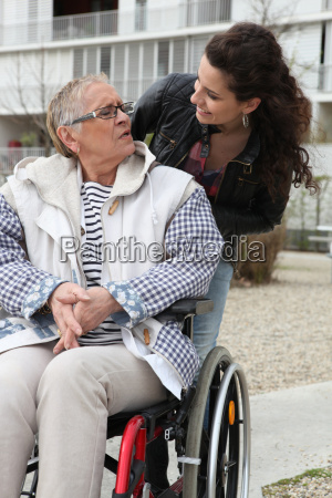 young woman helping a senior in