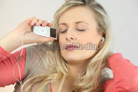 blonde with eyes shut listening to