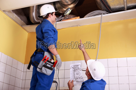 two technicians checking the air conditioning