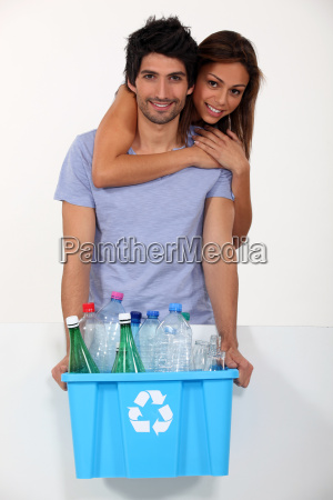 couple recycling plastic bottles