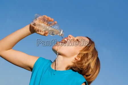 thirsty child drinking water from bottle