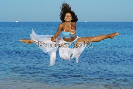 happy woman doing splits leap on