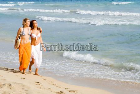 young women walking along seashore on