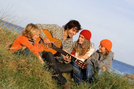 diverse family group playing guitar on