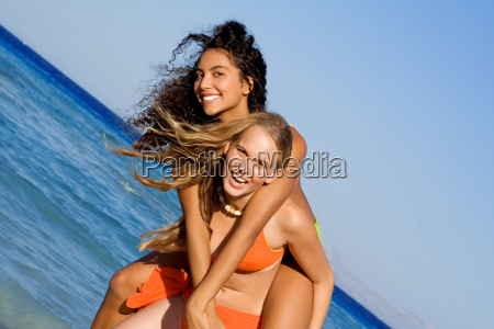 piggyback girls on beach summer vacation