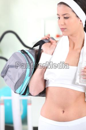 sporty woman holding bottle of water