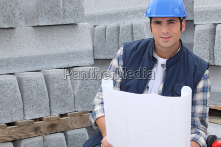 construction worker standing next to pallets
