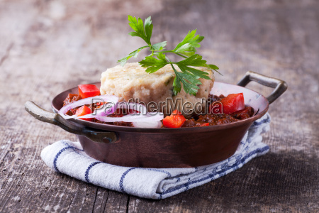 goulash with dumplings on a wooden