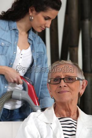 young woman vacuuming and senior woman
