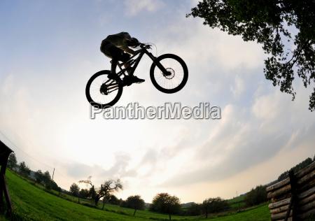 silhouette of a mountain bike jump
