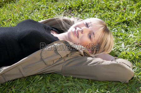 young woman lies on a meadow