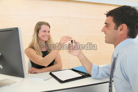 woman giving car key to businesssman