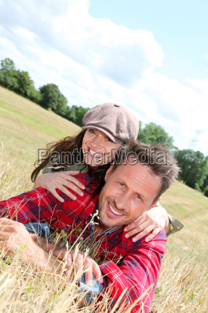 happy couple laying down meadow