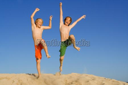 happy kids jumping on summer beach
