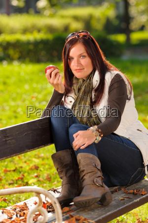 autumn attractive woman eat apple sunset