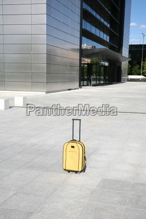 yellow suitcase in front of business