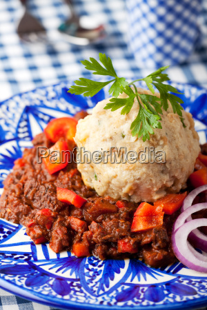 goulash with dumplings on a blue