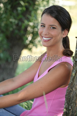 teenager sitting under tree