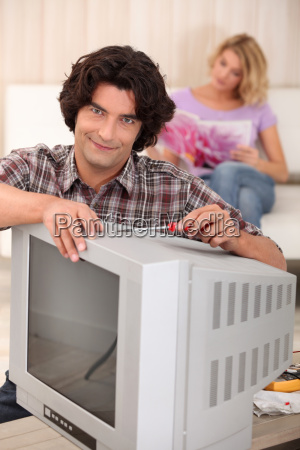 man fixing an old television