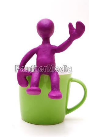 purple puppet of plasticine sitting on