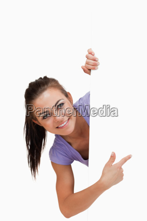 smiling young female pointing around the