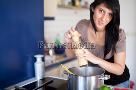 junge frau beim kochen von nudeln