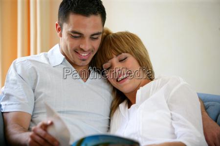 happy couple reading a magazine on