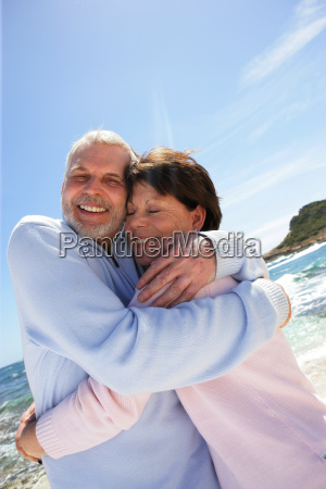 senior couple hugging at the seaside