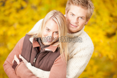 autumn happy couple hugging together in