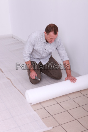 man unrolling underlay