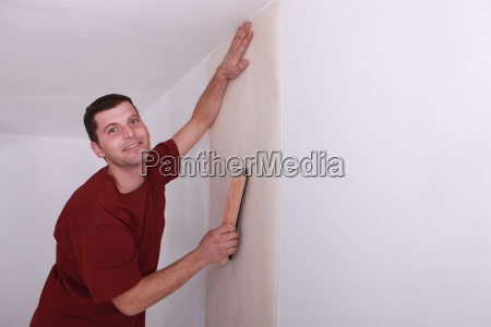 decorator smoothing down wallpaper with a
