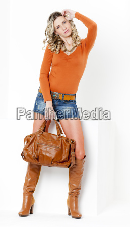 standing woman wearing fashionable brown boots