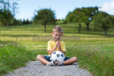 boy with soccer ball sits on