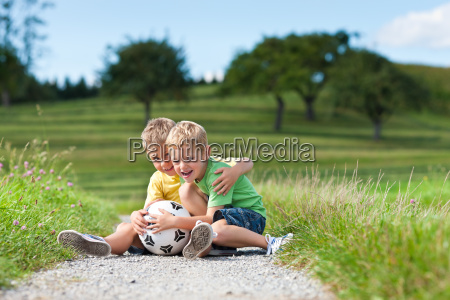 two children with football sitting on