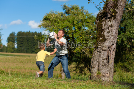 happy family is playing soccer in
