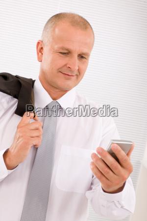 mature businessman hold phone close up