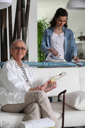 young woman ironing and senior woman