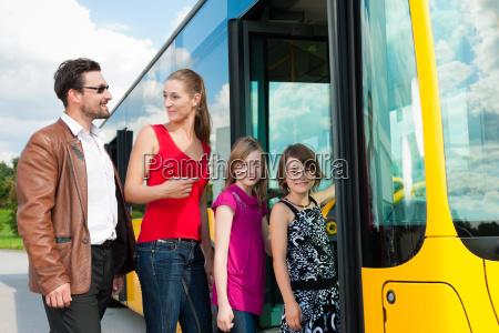 passengers climb into a bus
