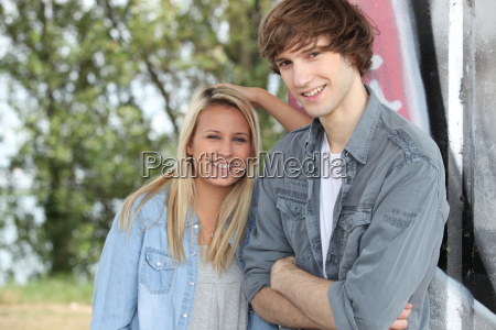 two teenagers stood outdoors leaning against