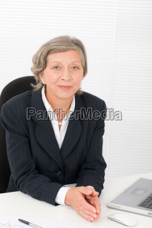 senior businesswoman smile sit behind office