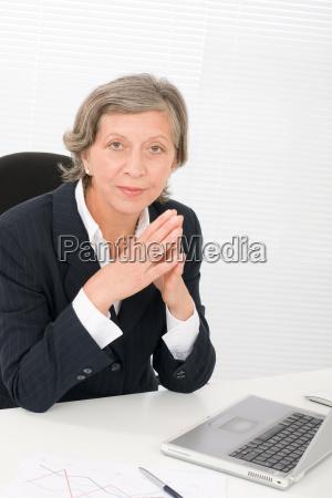 senior businesswoman sit behind office desk