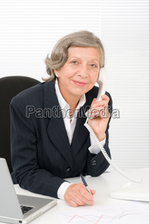 senior businesswoman smile sit behind office