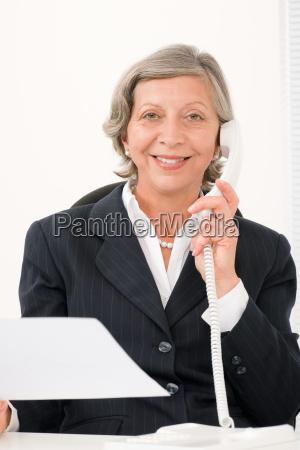 senior businesswoman on phone hold empty