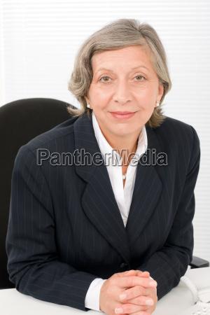 senior businesswoman professional behind table