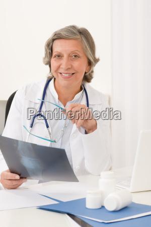 senior doctor female sit behind office