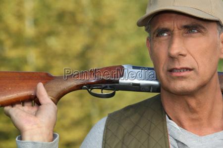 hunter holding his shotgun over his