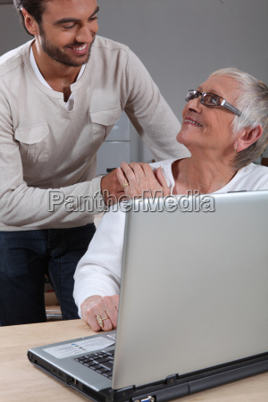 son helping mother on laptop